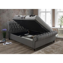 Load image into Gallery viewer, The Dublin Side Ottoman Bed in grey fabric. Lifestyle image of raised ottoman.