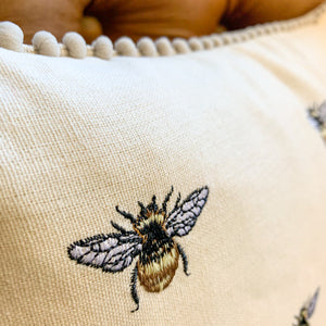 Embroidered Bee Cushion. Close up image of embroidered bee motif.