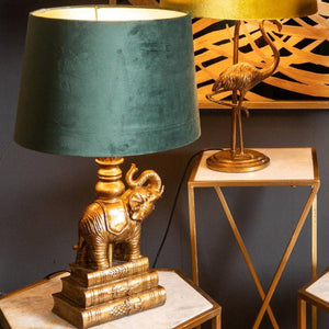 Antique Gold Elephant Table Lamp with emerald green velvet shade. lifestyle image.