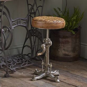 solid Iron base and a luxurious genuine tan leather seat with cog and crank mechanism for height adjustability
