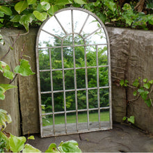 Load image into Gallery viewer, Outdoor garden mirror with metal frame and arched top. Lifestyle image.