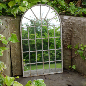 Outdoor garden mirror with metal frame and arched top. Lifestyle image.