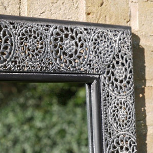 Outdoor Moroccan Garden Mirror with ornate metal frame. Close up of metal frame.