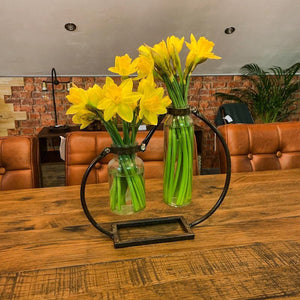Lifestyle image of Industrial style double vase with an attractive metal frame. The vase has flowers.
