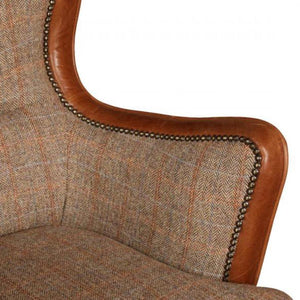 Elliot Armchair in Game keeper harris tweed and brown italian cerato leather. Close up of arm with stud work.