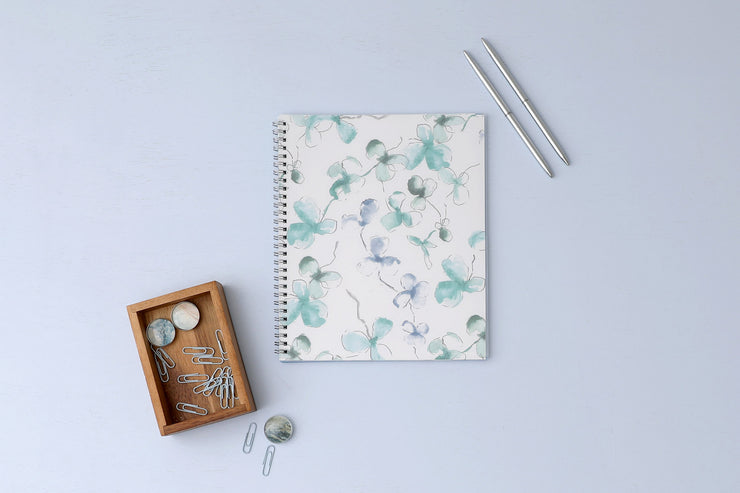 Blue Sky's Lindley monthly planner for 2021 featuring a white background and brushed clovers in shades of blue and silver twin wire-o binding