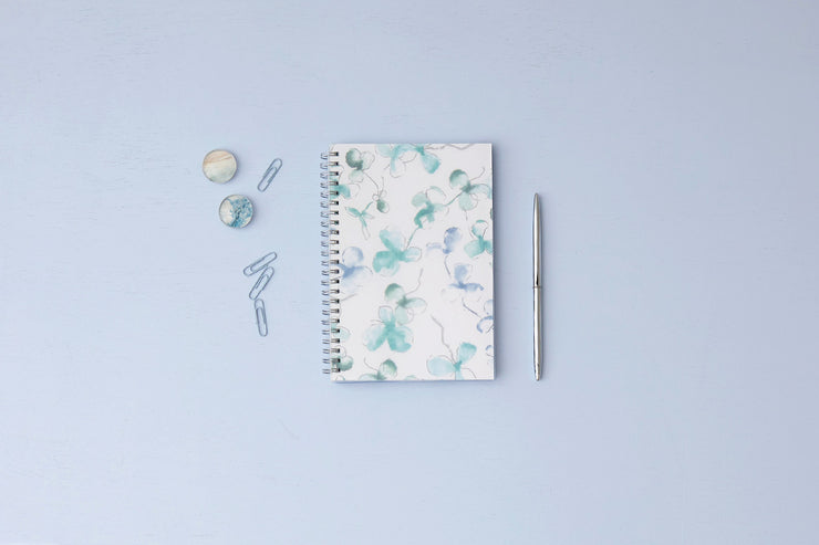 Blue Sky's Lindley weekly monthly planner for 2021 featuring a white background and brushed clovers in shades of blue and silver twin wire-o binding