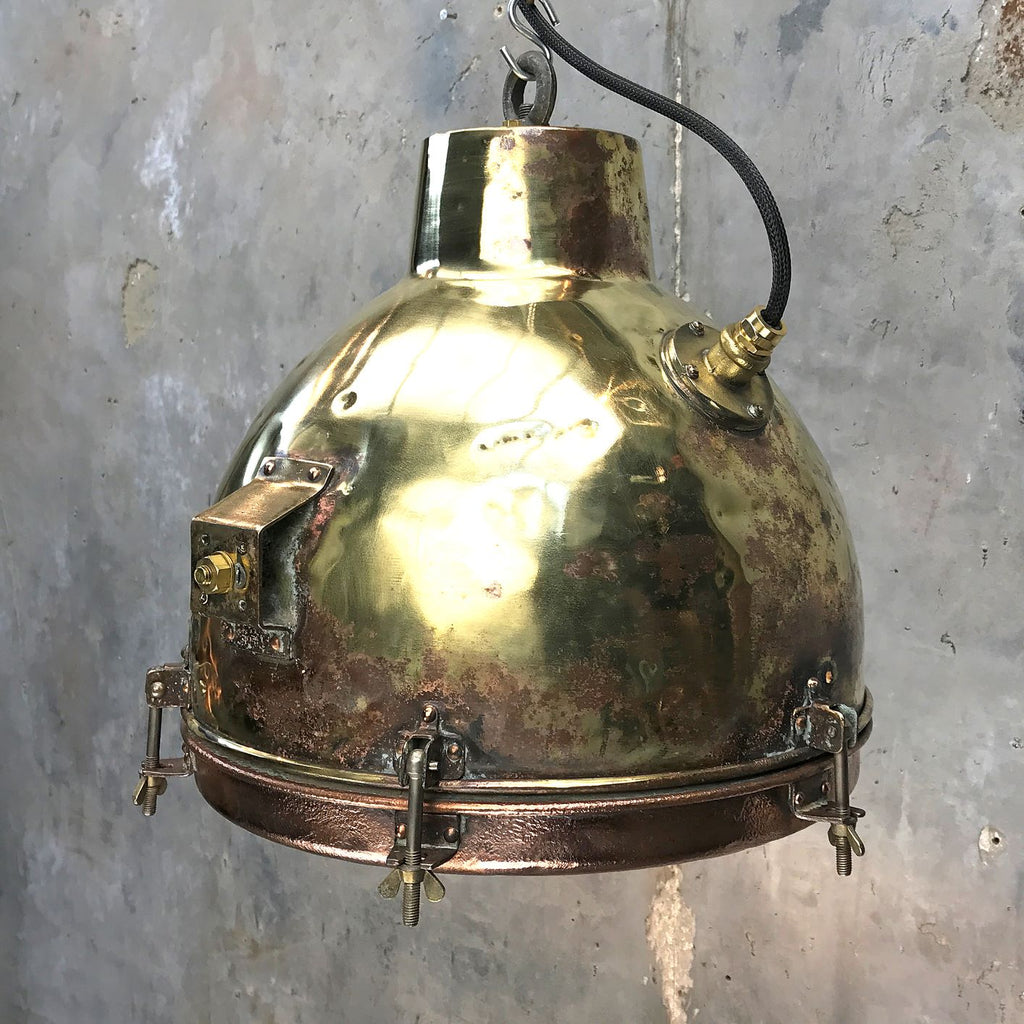 A retro industrial brass and copper dome ceiling pendant with convex glass.