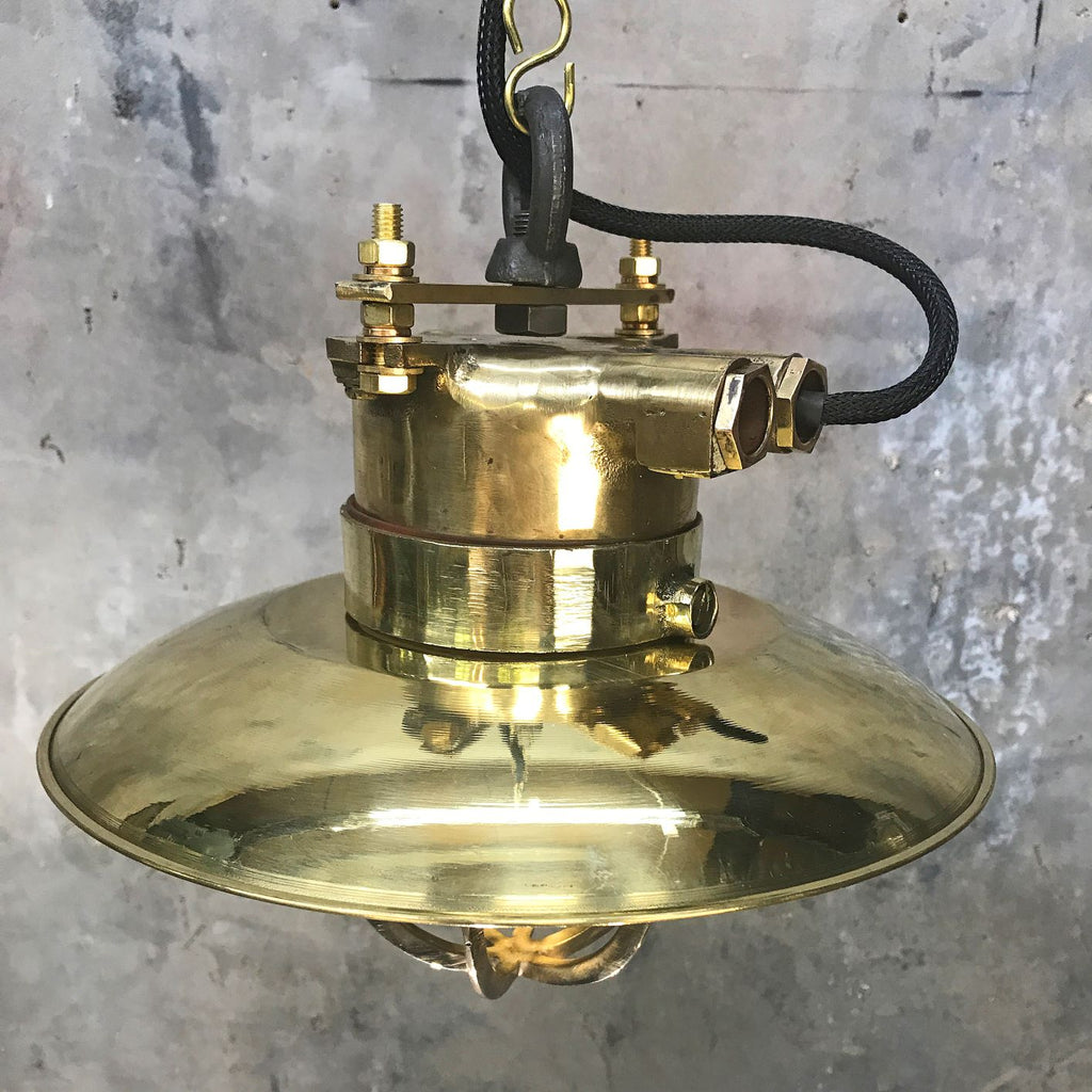 A vintage industrial brass explosion proof ceiling pendant light with protective cage.