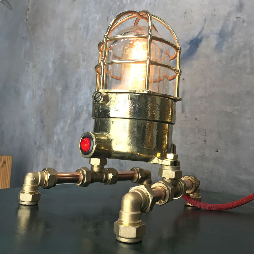 A vintage industrial 1970's brass explosion proof passage way light modified into a steampunk style table lamp.