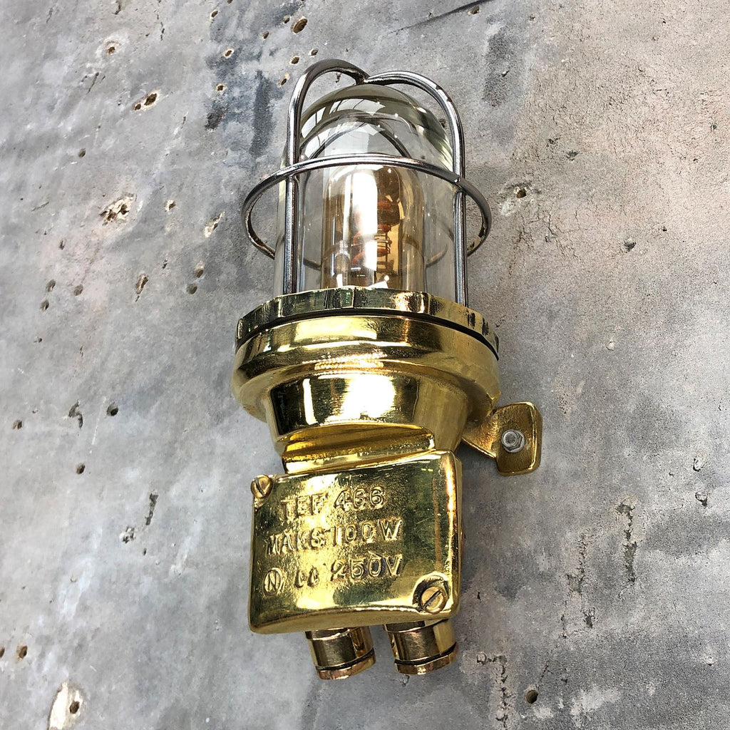 A retro industrial brass outdoor wall light with protective glass shade and cage