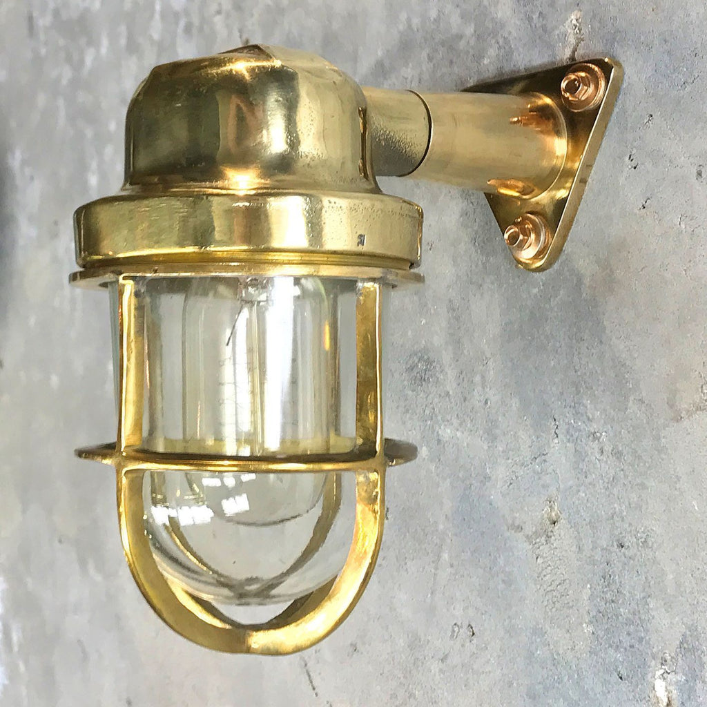 A reclaimed retro industrial solid brass 90 degree outdoor wall light with protective cage.