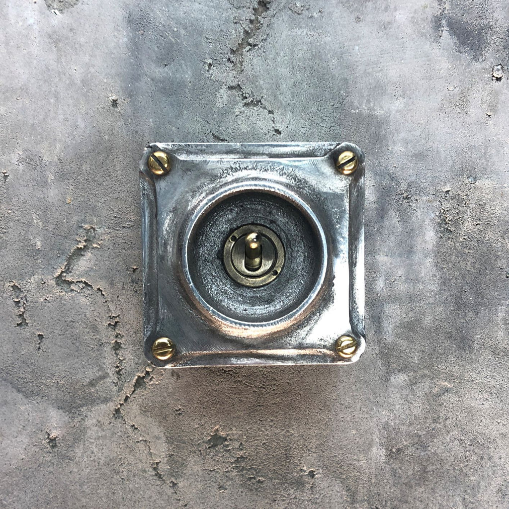A single industrial light switch.  Manufactured from recycled alloy wheels.