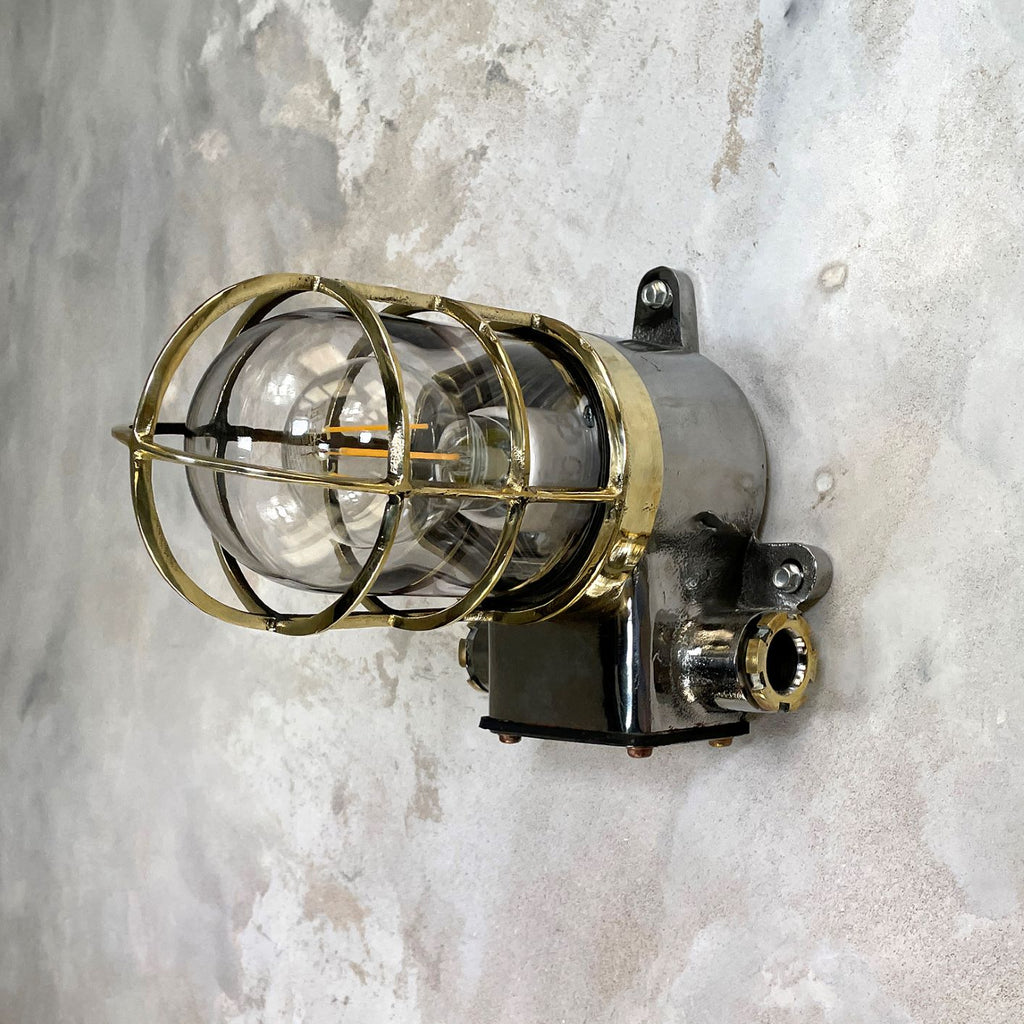 A vintage outdoor iron wall light with industrial style brass cage.