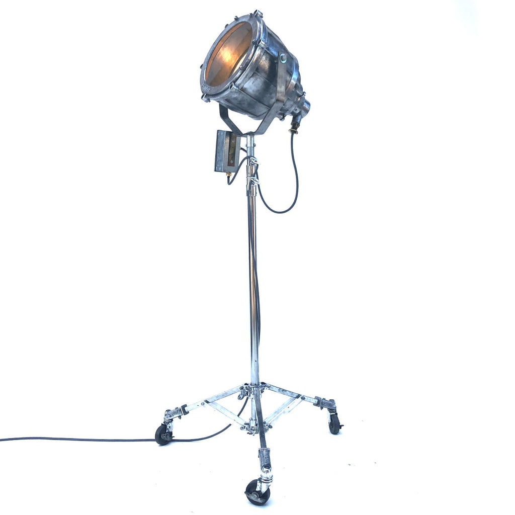 Retro industrial aluminium explosion proof cargo light with a telescopic Matthews theatre stand to create a large bespoke floor standing lamp.