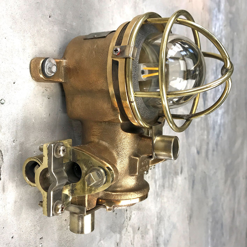A small vintage industrial cast bronze flameproof wall light with protective cage.