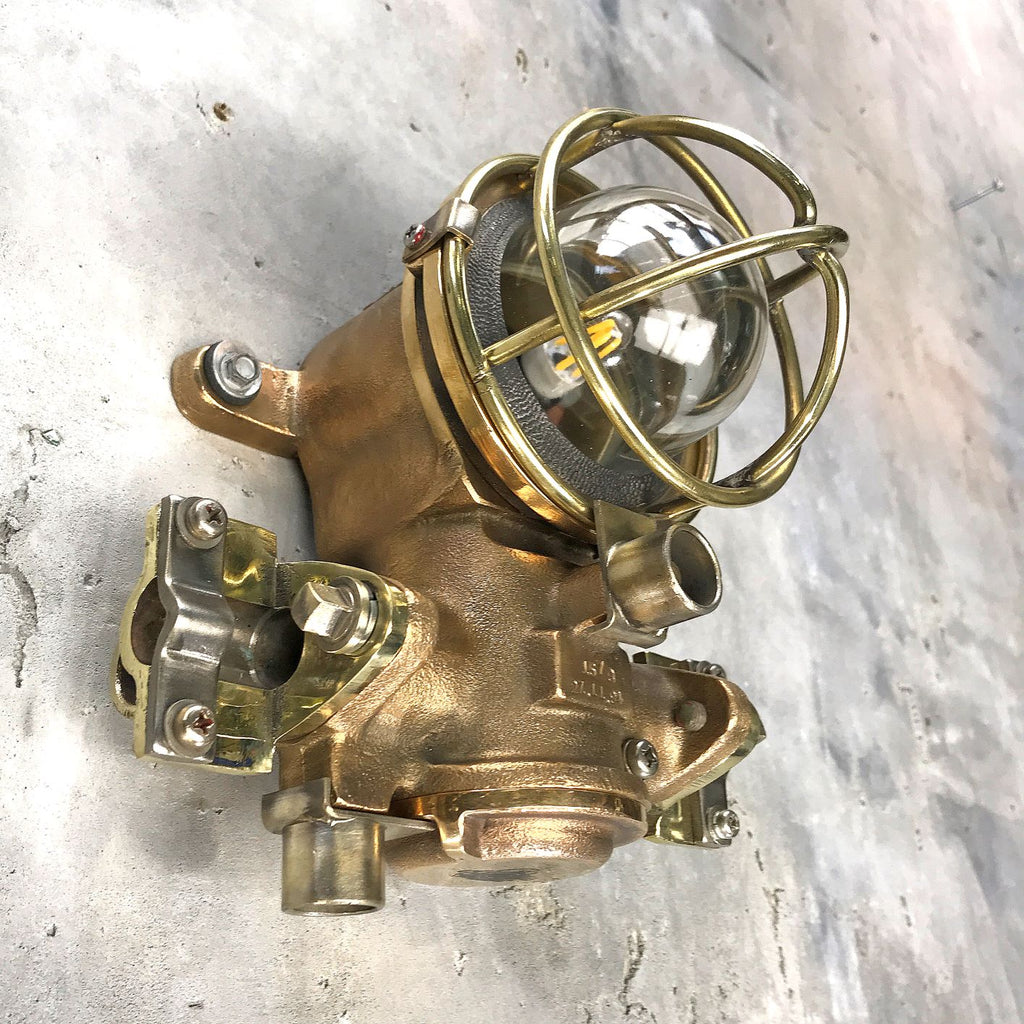 A small vintage industrial cast bronze flameproof wall light with protective cage by Kokosha
