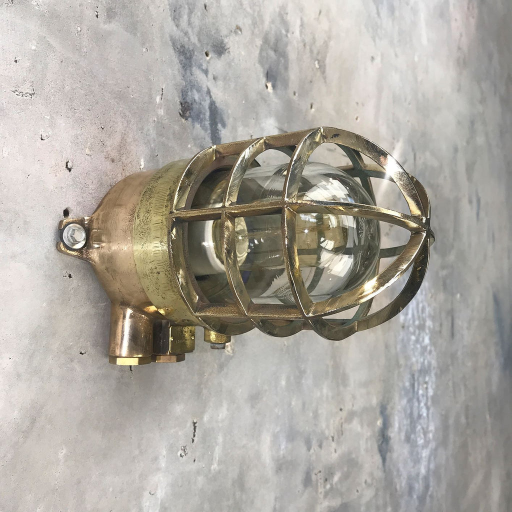 A vintage industrial bronze and brass outdoor wall light fixture with protective cage by Wiska.