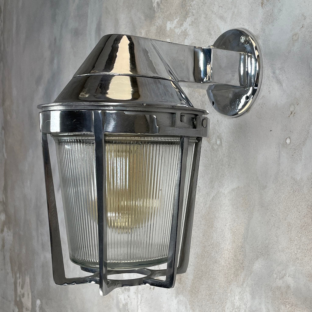 A vintage cast aluminum wall light with prismatic glass shade and industrial style protective cage by Appleton
