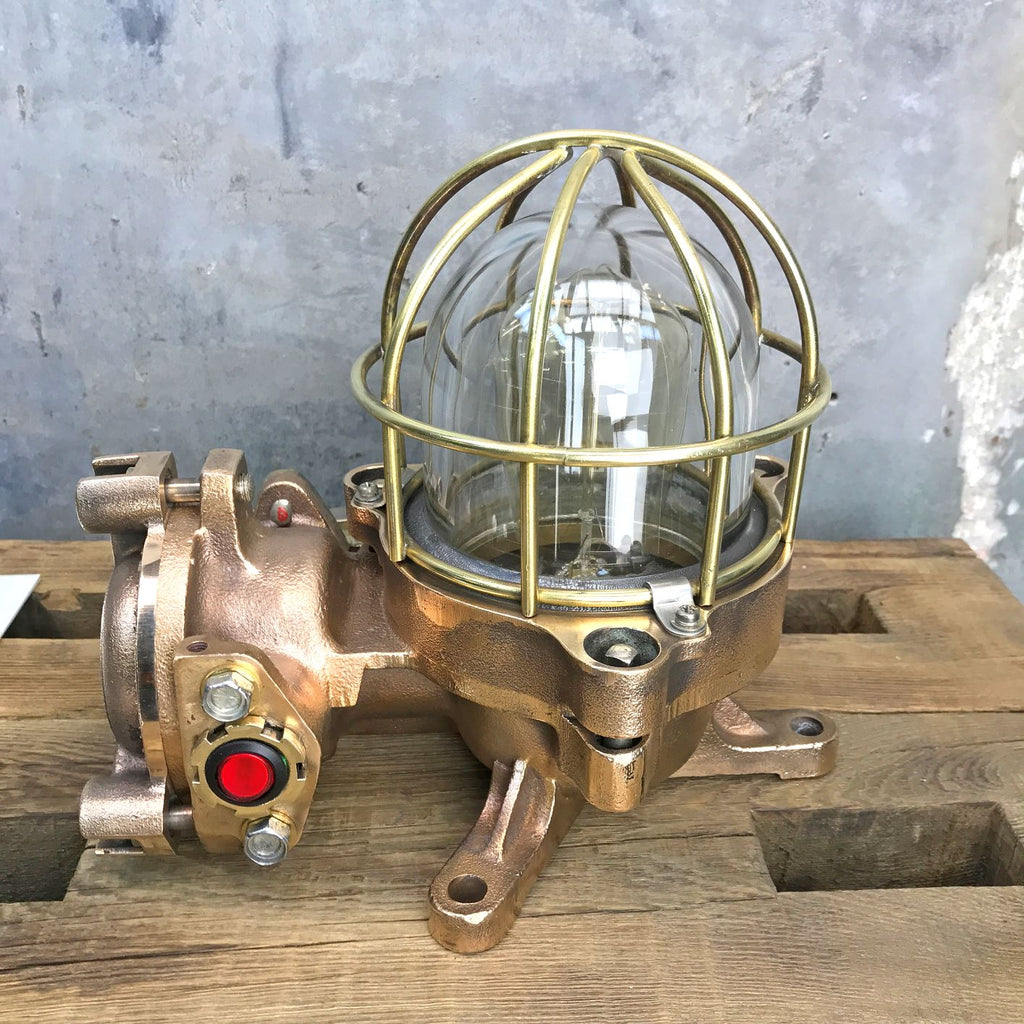 A vintage industrial flameproof cast copper table lamp with braided cable and red glow switch and protective cage