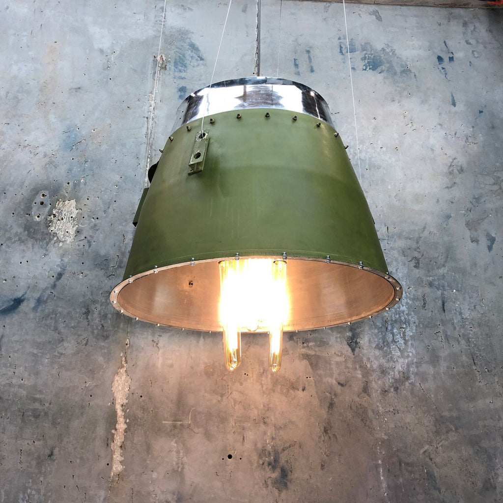 A large industrial green lamp shade originally a jet engine cowling from a bombardier learjet