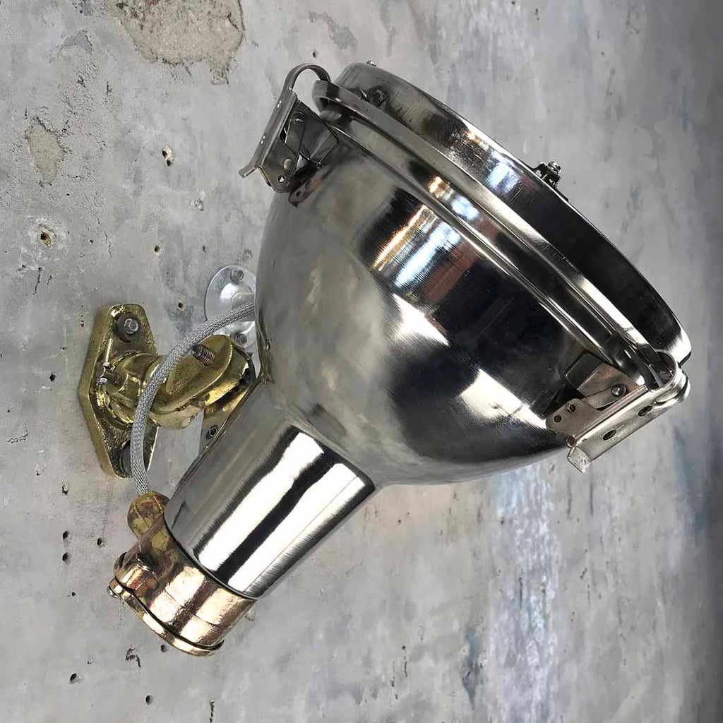 A retro industrial chrome and cast brass directional wall light.