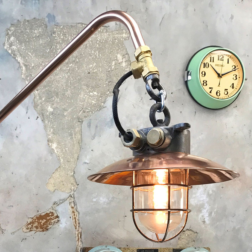 A vintage industrial copper cantilever wall light with a copper & iron cage pendant