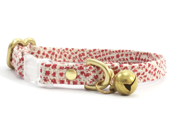 Red breakaway safety cat collar in polka dot fabric with transparent buckle and solid brass bell, by Noggins & Binkles