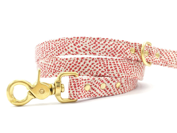 Stylish red dog lead/leash in luxury polka dot linen and cotton fabric with solid brass trigger snap hook, d ring and rivets, made in the UK by Noggins & Binkles