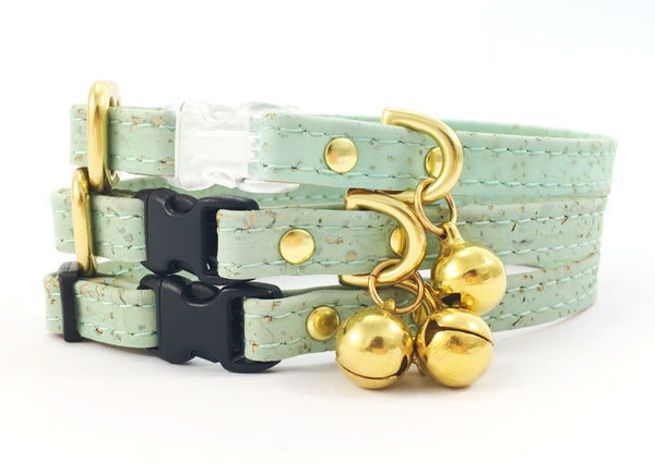 Luxury designer pastel mint green vegan cork 'leather' breakaway safety cat collar with solid brass bell, can be customised with a black or transparent breakaway safety buckle and choice of solid brass or black sliders, made by Noggins & Binkles