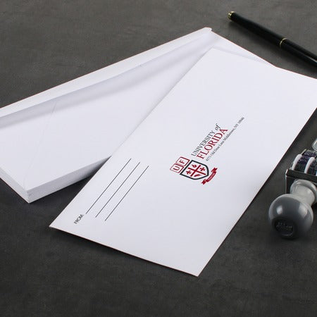 #9 full color printed envelope on desk with pen and date stamp.