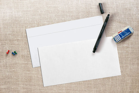 white linen envelopes on desk with pen and eraser