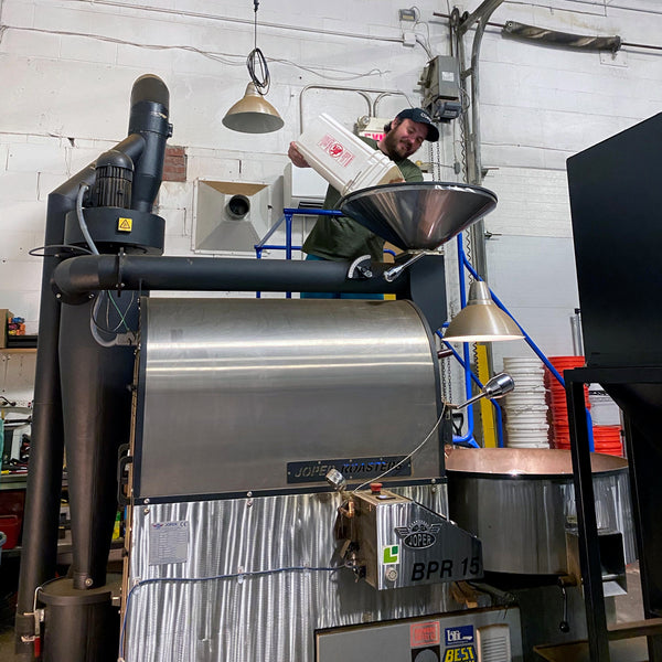 Bruce pours green beans into the roaster