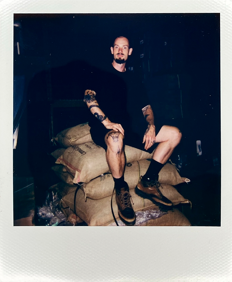 Portrait of Sam James sitting on a throne of coffee bean bags