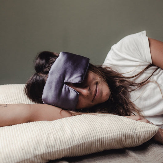 Woman sleeping with sleep stone mask around her eyes