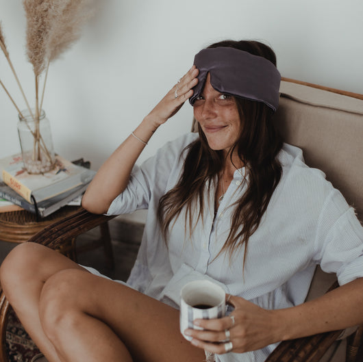 Woman drinking a cup of coffee with sleep stone mask around her head