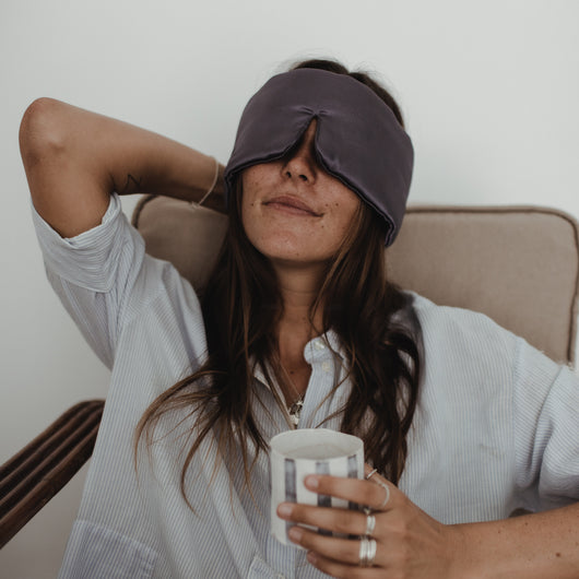 Woman drinking a cup of coffee with sleep stone mask around her eyes