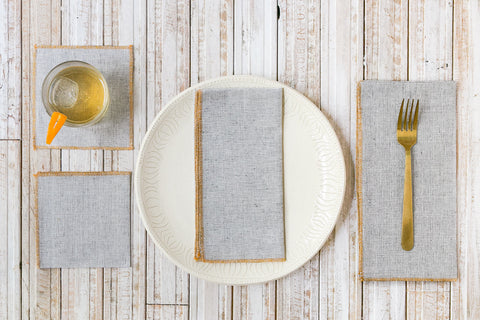 Dot and Army cloth napkin and coaster sizing chart, 4 napkin sizes next to a glass and plate on a wooden table.