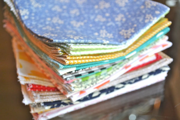 bargain stack of cloth napkins with variety of patterns on wooden table