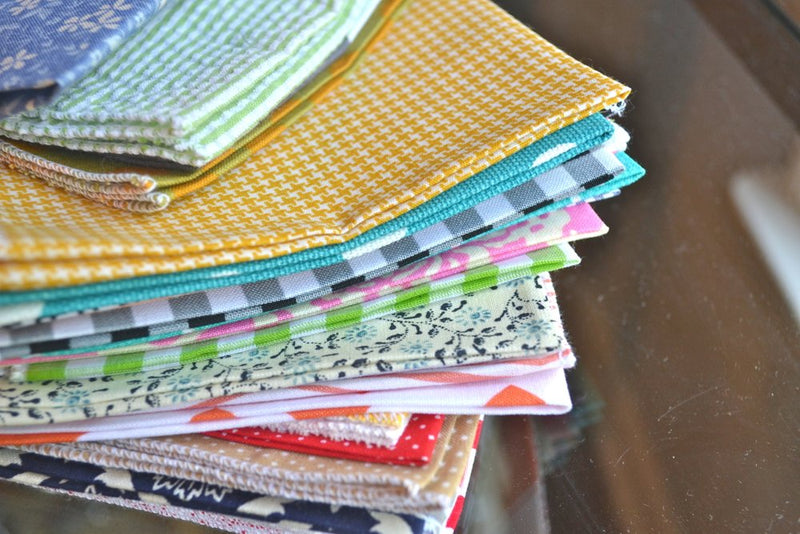 bargain stack of cloth napkins with variety of patterns close up