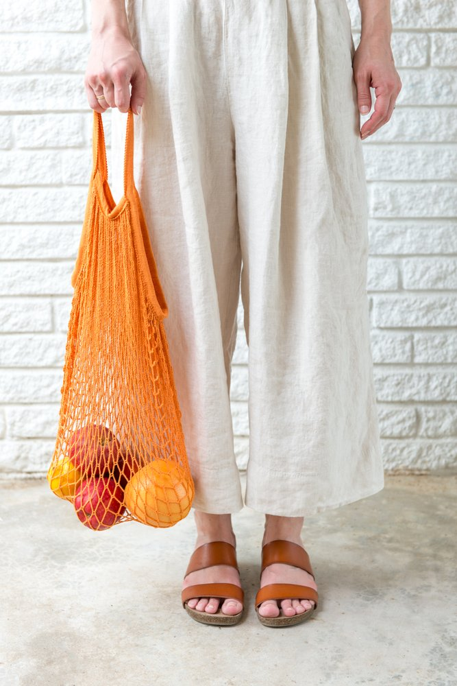 woman in a neutral colored baggy pants holding an orange reusable produce bag in front of a white brick wall