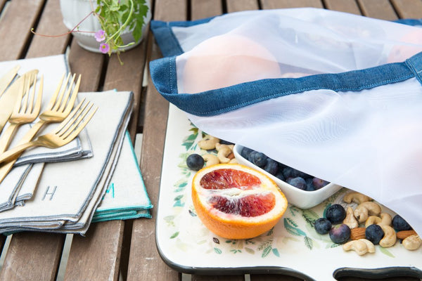 mesh food net with denim border covering food on picnic table