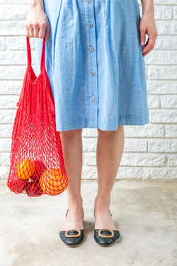 woman in a blue dress holding a red reusable produce bag in front of a white brick wall