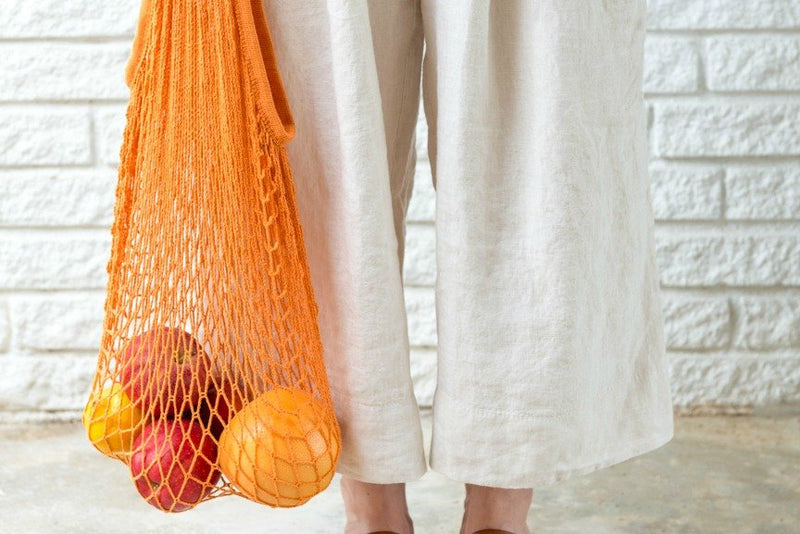 orange reusable produce bag next to womans legs in front of a white brick wall