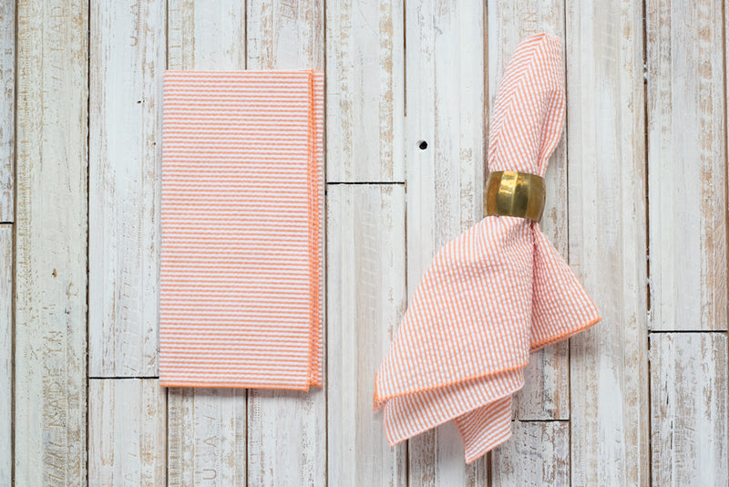 orange colored seersucker cloth napkins on table