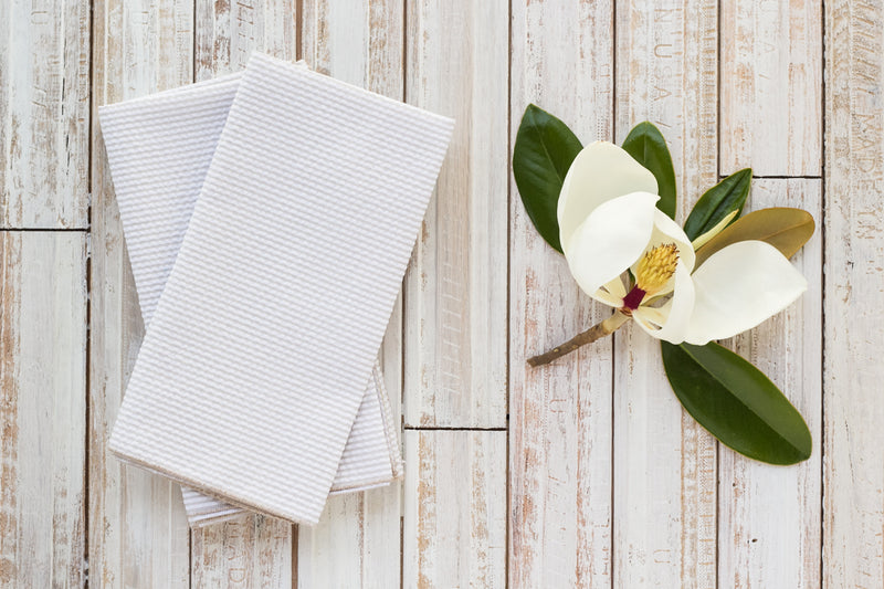 khaki colored seersucker cloth napkins on table with magnolia