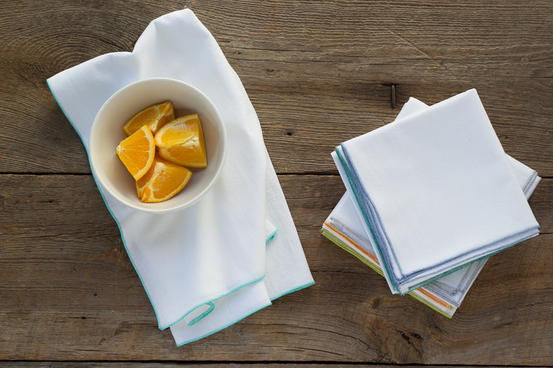 flour sack towels with fruit on wooden table