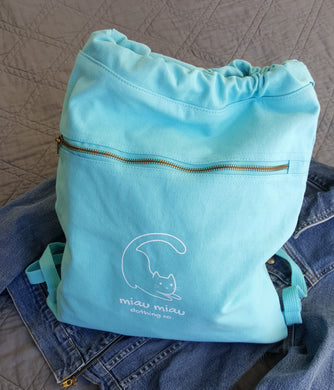 Vintage washed aqua blue cinch style backpack bag with Miau Miau Clothing Co. logo