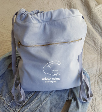 Vintage washed blue cinch style backpack bag with Miau Miau Clothing Co. logo