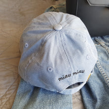 "Vintage washed blue baseball hat with embroidered words ""Miau Miau"" on back."